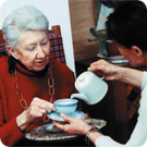 A carer pours the tea for her patient