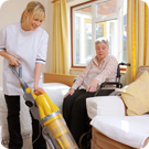 A carer vacuums the carpet for her patient